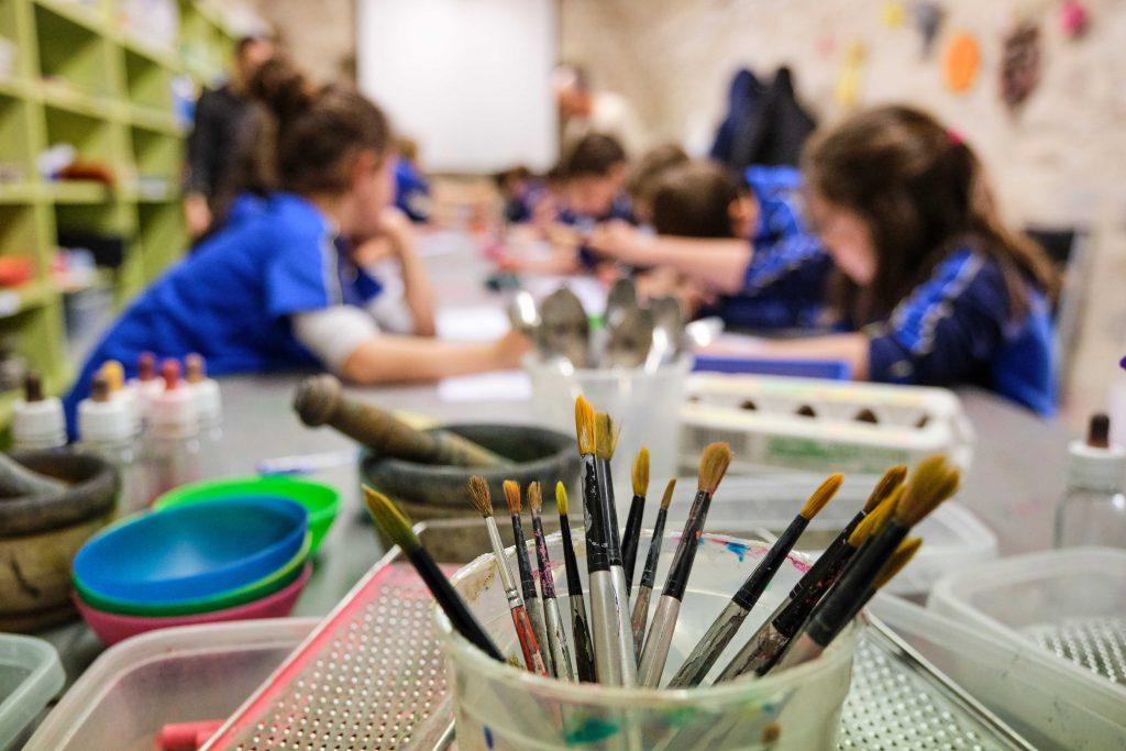 Grup de nens entaulats, amb pinzells per pintar