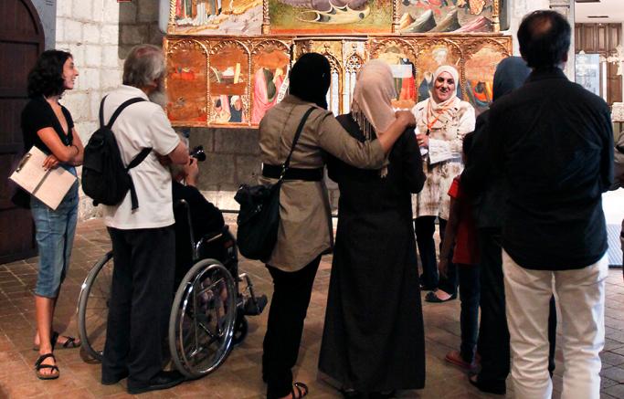 Un grup de persones escolten la visita guiada d'una persona d'origen àrab