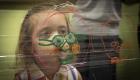 Nena davant d'un dibuix a un vidre