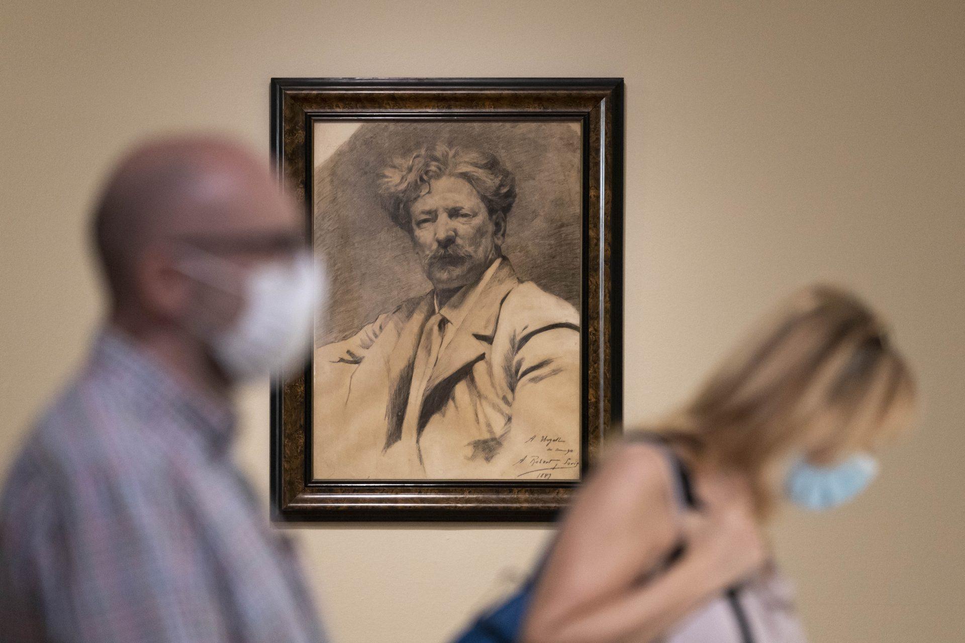 Dues persones amb mascareta passant davant d'un quadre d'un retrat