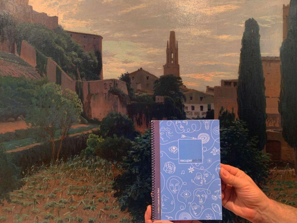 Unes mans amb la llibreta recuperart-19 i un quadre de Girona de fons.